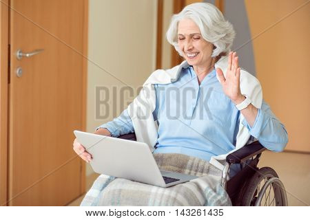Hay. Positive and happy woman sitting in wheelchair and using laptop and webcam