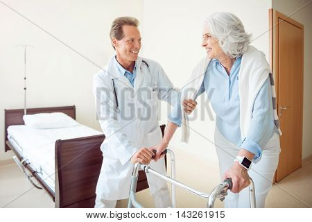 Physically rehab. Cheerful and merry senior woman with walking frame and her doctor helping her