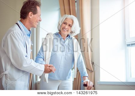 Nice aging. Smiling doctor helping cheerful and content senior patient