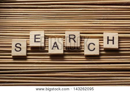 search word on wooden cube at wood background.