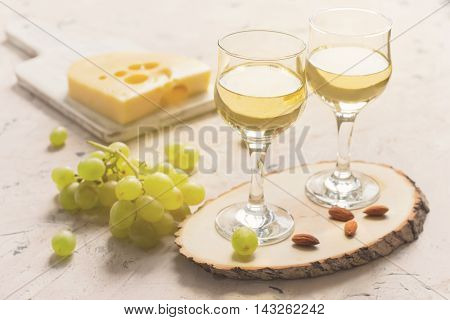 Two glasses of white wine with grapes cheese and nuts.