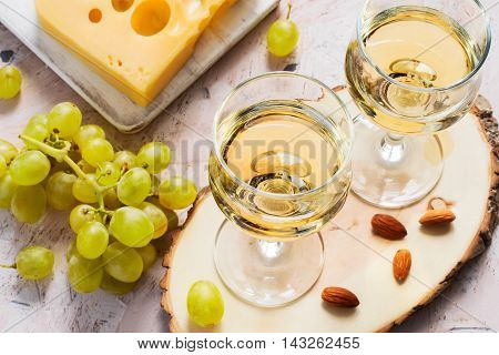 Glasses of white wine grapes and nuts.
