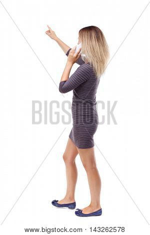 back view of pointing young beautiful  woman and using a mobile phone. girl  watching. Rear view people collection.  backside view of person.  Isolated over white background. Blonde in violet short