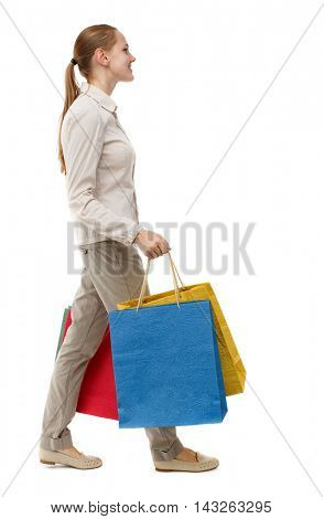 side view of going  woman  with shopping bags . beautiful girl in motion.  backside view of person.  Rear view people collection. Isolated over white background. Skinny girl in white jeans walks past