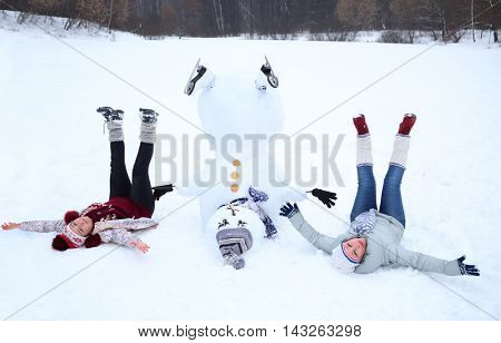 Upside down snowman with hat and two happy women at winter day