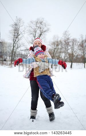 Happy woman circles her little handsome son at snowy winter day