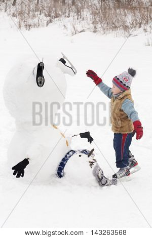 Little handsome boy plays with upside down snowman at winter day