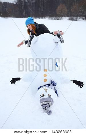 Upside down snowman with hat and girl teenager at winter day