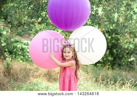 Smiling baby girl 5-6 year old holding big balloons over nature background. Looking at camera. Wearing stylish dress and unicorn headband.
