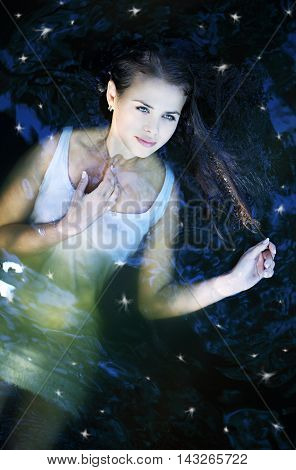 Young beautiful girl in a dark river water, top view