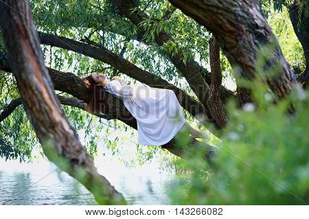 Beautiful woman in white dress lying on a tree over the river