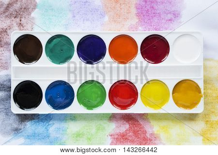 Palette of watercolors on colorful background closeup