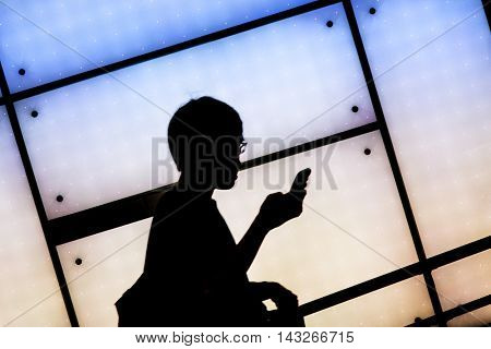 Street photography Tokyo. Man with mobile phone backlit by illuminated panel in subway station