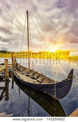 Viking harbor with old boat in Denmark at sunset