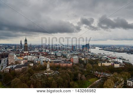 HAMBURG, GERMANY - MARCH 27, 2016: Scenic panorama over Landungsbruecken, New Elbphilharmonie, river Elbe, the famous Michel, and docks in Hamburg -