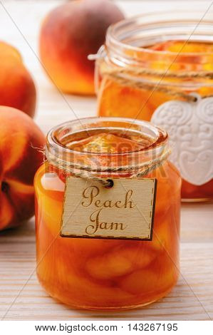 Peach jam in glass jars on white wooden background.