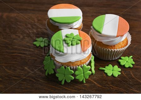 Tasty cupcakes with clover on wooden background. Saint Patrics Day concept