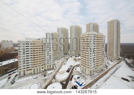 MOSCOW - JAN 30, 2015: Cars, high residential buildings, clouds at Elk Island housing complex
