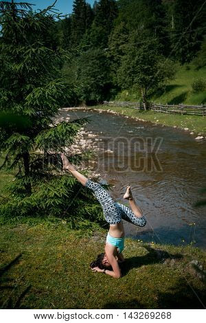 Young Beautiful Girl With Nice Body Stands On The Head During Yoga On The Shore Of A Mountain River.