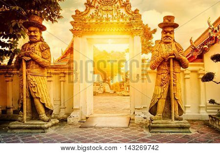 Classical Thai architecture in public temple at dramatic orange sunset sky Bangkok Thailand. Guardian Statues stand guard at a gate of Wat Pho. Soft focus.