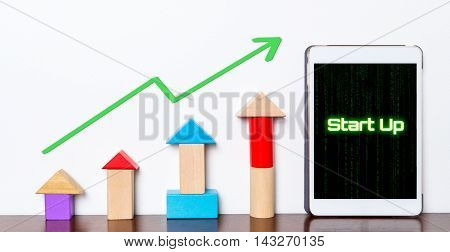 Start up Business success growing concept on tablet. Toy block rise up with Start up Model planning stepping up diagram graph.