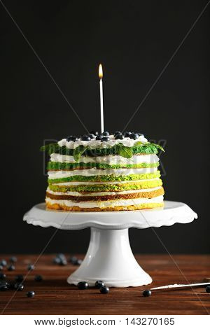 Delicious cake with candle on stand on dark background