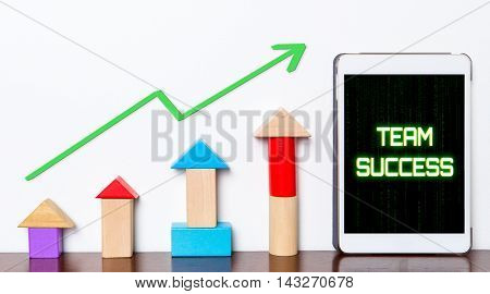 Team work success growing concept on tablet. Toy block rise with Team success diagram graph. Tablet with hi tech tech text Business team success rising up.