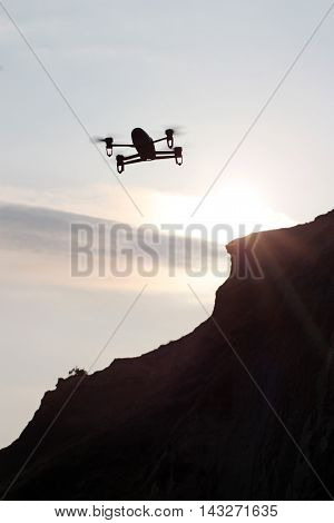 Flying drone silhouette against the sunset sky