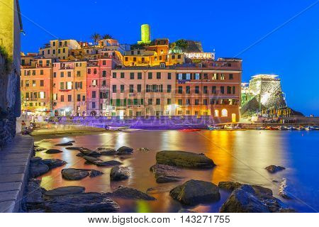 Night fishing village Vernazza with lookout tower of Doria Castle to protect the village from pirates, Five lands, Cinque Terre National Park, Liguria, Italy.