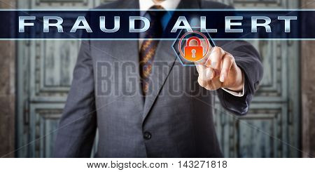 Male inspector touching FRAUD ALERT on interactive touch screen. Information technology and criminal offense concept. A virtual orange red padlock lights up as warning sign of an imminent deception.