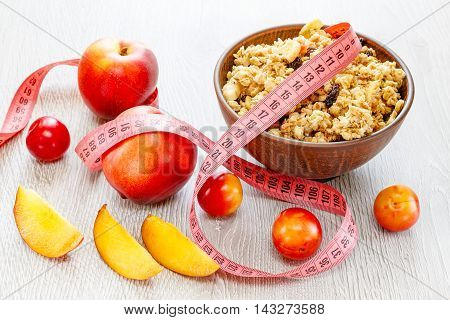 Beautiful plate with muesli plums peach and meter tape