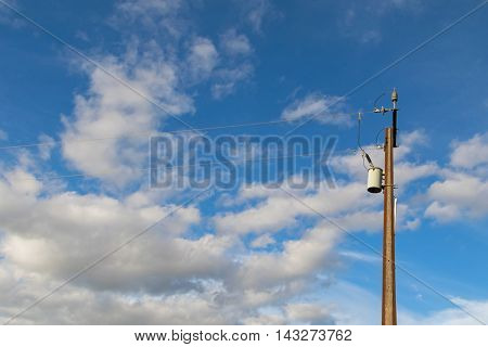 Transformer on a electric power pole (utility pole) made of 2 steel joists against blue sky with copyspace, in South Australia