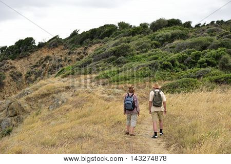 Woman and man with backpacks walking on the mountain and enjoying the nature