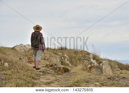 Woman with backpack walking on the mountain and enjoying the nature