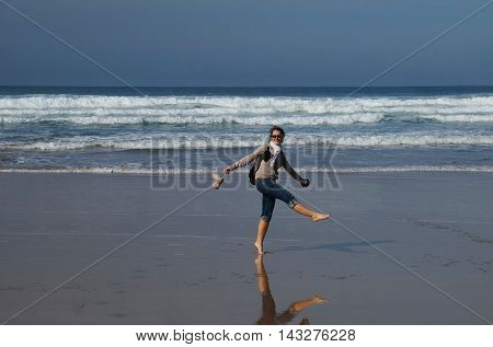 One women fools around on the wet sand in front of white foamy waves enjoying the summer, the ocean and the vastness and freedom of the ocean.