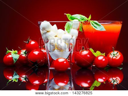 Tomatoes tomato juice and mozzarella cheese on a red background with basil leaves