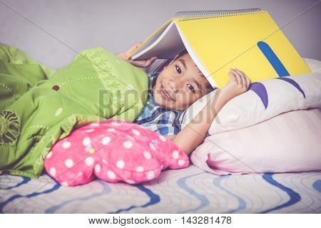 Close Up. Asian Boy Covering Head With Book And Smiling. Education Concept. Vintage Tone Effect.