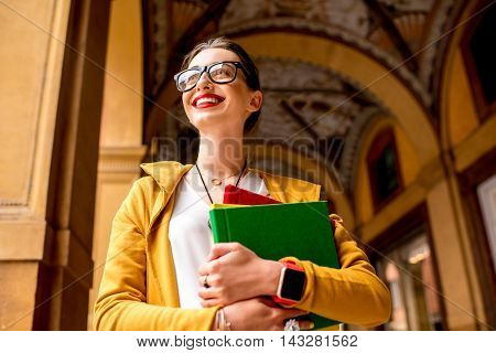 Portrait of a young female student dressed casually in the famous arched galleries in Bologna city in Italy. Bologna is student city and home to the oldest university in the world