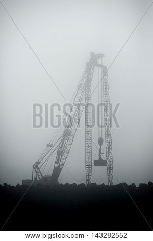 A crane lifts a heavy weight with which it compacts the soil of a new dock in the harbour.