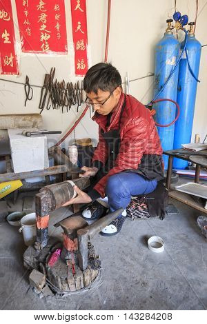 Heqing, China - March 16, 2016: Bayi Man Making A Silver Pot. Heqing Is Famous For The Artigianal Pr