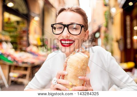 Young woman sitting with panini sandwich with prosciutto at the cafe outdoor on the street in Bologna city