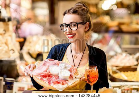 Young woman sitting near the food shop with traditional italian aperitif on the blurred food showcase background in Bologna city. Bologna is the gastronomic center of Italy