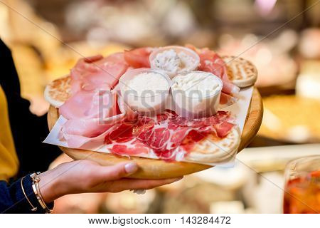 Female hands holding traditional italian aperitif with proscioutto, mortadella sausage and cheese on the wooden board with blurred food on the background.