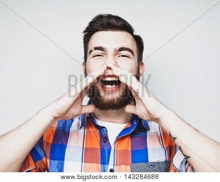 life style and people concept: Portrait of a handsome young man yelling, over a gray background