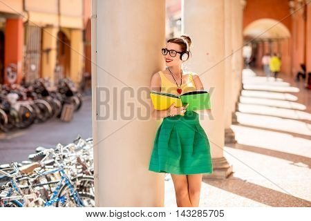 Young female student dressed casually with colorful books listening to the music during the break outdoor in the gallery in Bologna city