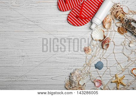 Flip flops with sea shells on wooden background