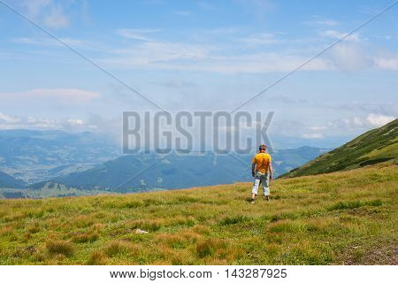 Hiker man goes on a alpine meadow. Back view. Wonderful evening in the mountains.
