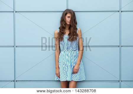 Outdoor Portrait Of Happy Young Beautiful Brunette Woman In Striped Summer Dress Posing Against Stee
