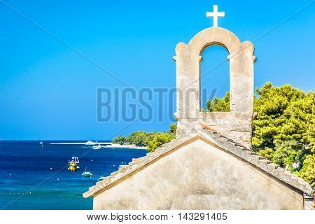 Small chapel with marble seascape and famous Golden Cape (Zlatni Rat) beach in background, Croatia summertime.