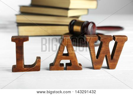 Word law with judges gavel and legal books on wooden background